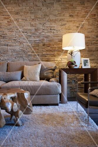 Wohnzimmer in Naturtönen mit Steinwänden, Sofa, Hochflorteppich ...