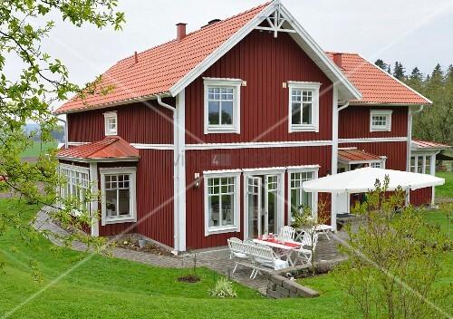 rot weisses schwedisches holzhaus mit terrasse in gr ner landschaft bild kaufen living4media. Black Bedroom Furniture Sets. Home Design Ideas