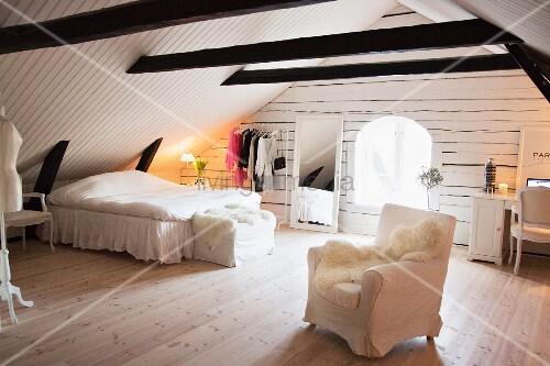 feminines weisses schlafzimmer in ausgebautem dachstuhl mit dunklen holzbalken bild kaufen. Black Bedroom Furniture Sets. Home Design Ideas