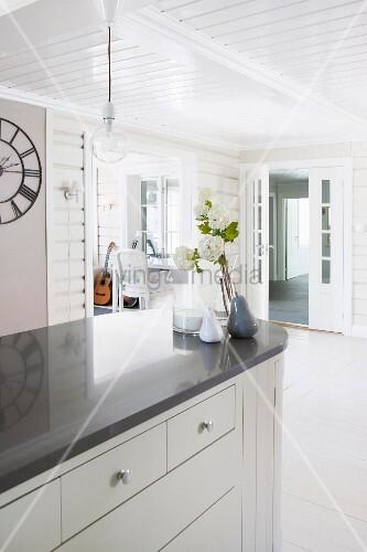 freistehende theke mit abgerundeter ecke und dunkler arbeitsplatte in offener k che mit weisser. Black Bedroom Furniture Sets. Home Design Ideas