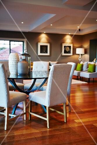weisse gepolsterte st hle an rundem glastisch mit verschiedenen vasen im hintergrund sessel in. Black Bedroom Furniture Sets. Home Design Ideas