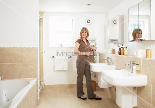 Frau In Badezimmer Mit Zwei Einzelwaschbecken Unter Spiegelschränken,  Sandfarbene Fliesen Auf Boden Und Wänden