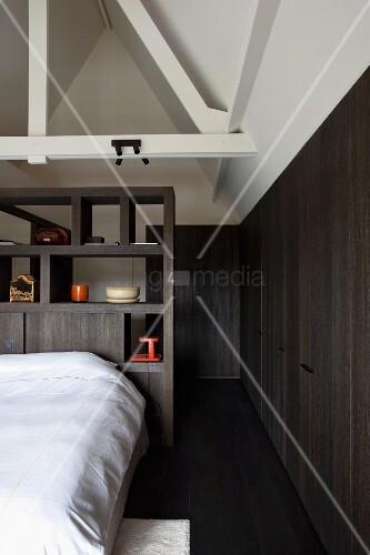 schlafzimmer unter dem ausgebautem dach bett mit weisser bettw sche vor dunklem holzregal als. Black Bedroom Furniture Sets. Home Design Ideas
