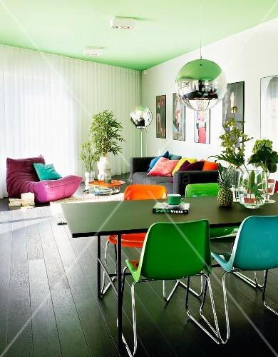 farbige kunststoff st hle an schwarzem tisch unter kugel. Black Bedroom Furniture Sets. Home Design Ideas