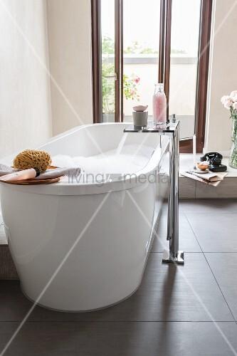 freistehende badewanne mit standarmatur auf schieferboden vor balkont r bild kaufen living4media. Black Bedroom Furniture Sets. Home Design Ideas