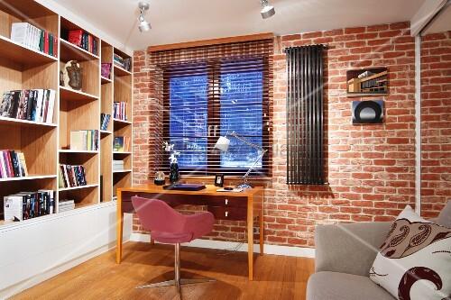 schlichter arbeitsplatz am fenster rosa bezogener drehstuhl vor holztisch an ziegelwand. Black Bedroom Furniture Sets. Home Design Ideas