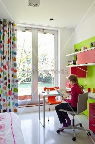m dchen am schreibtisch vor balkont r mit bodenlangem. Black Bedroom Furniture Sets. Home Design Ideas
