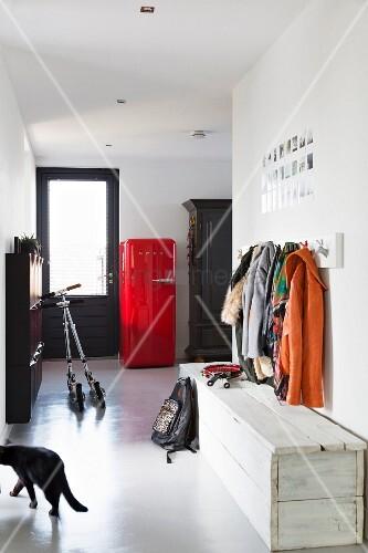 gangbereich mit schlichter truhenbank aus weiss lackiertem holz unter garderobe im hintergrund. Black Bedroom Furniture Sets. Home Design Ideas