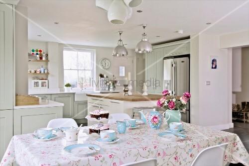 gedeckter fr hst ckstisch mit hellblauem geschirr im hintergrund offene k che im landhausstil. Black Bedroom Furniture Sets. Home Design Ideas