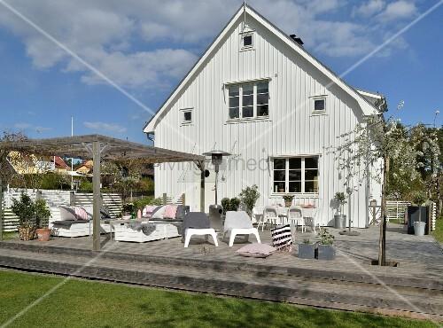 idyllisches wei es schwedenhaus mit gro er holzterrasse und wei en outdoorm beln bild kaufen. Black Bedroom Furniture Sets. Home Design Ideas