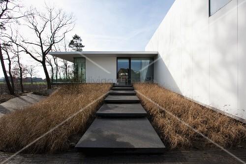 podestartige treppenstufen aus stein zwischen vertrockneten grasfl chen im hintergrund moderner. Black Bedroom Furniture Sets. Home Design Ideas