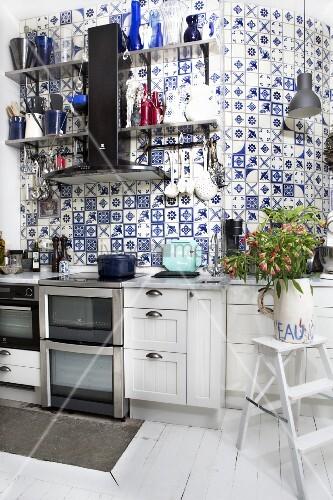 Weiße Küchenzeile vor hoher gefliester Wand mit traditionellen weiss blauen Fliesen im