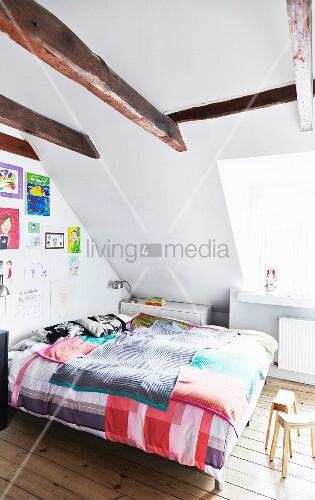 schlafzimmer mit sichtbaren balken bunten kinderzeichnungen an der wand und naturbelassenem. Black Bedroom Furniture Sets. Home Design Ideas