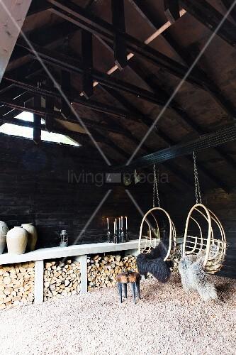 zwei korbh ngesessel mit schaffellen an scheunenbalken aufgeh ngt holzlagerplatz an. Black Bedroom Furniture Sets. Home Design Ideas