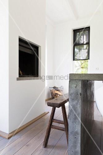 betontisch und rustikale holzbank vor offenem kamin bild kaufen living4media. Black Bedroom Furniture Sets. Home Design Ideas