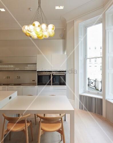 essplatz mit designer holzst hlen unter pendelleuchte mit glaskugel schirmen seitlich erker in. Black Bedroom Furniture Sets. Home Design Ideas