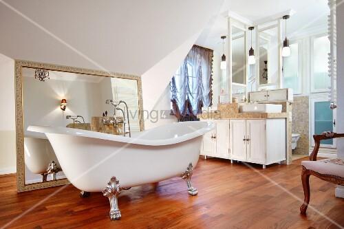 freistehende badewanne auf versilberten klauenf en vor gerahmtem spiegel auf holzboden in. Black Bedroom Furniture Sets. Home Design Ideas