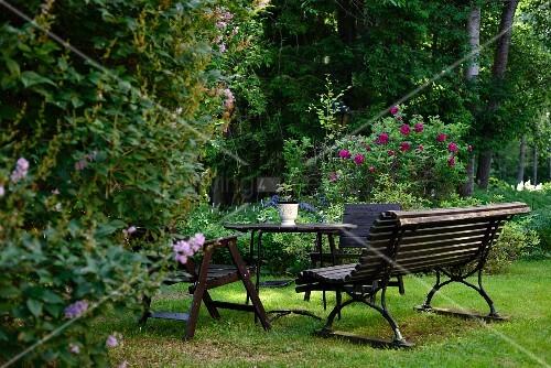 parkbank tisch und holzst hle auf rasen in park hnlichem garten mit bl henden stauden bild. Black Bedroom Furniture Sets. Home Design Ideas
