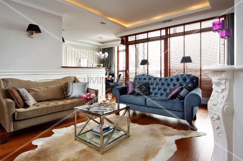 sofa in beige und blau um couchtisch auf tierfell am boden