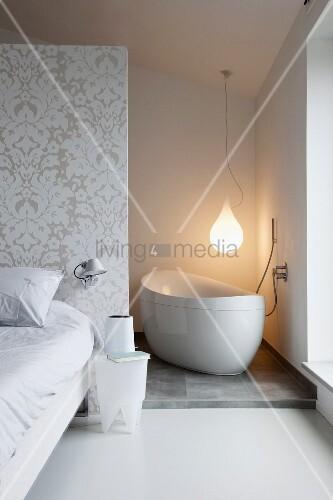 bett und beistelltisch vor raumteiler in zimmerecke freistehende badewanne unter pendelleuchte. Black Bedroom Furniture Sets. Home Design Ideas