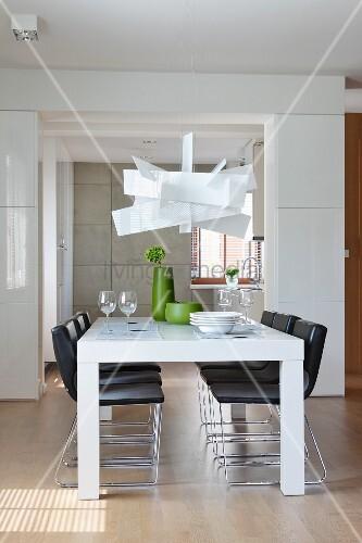 designerlampe ber weissen esstisch und schwarze st hle in offenem wohnraum bild kaufen. Black Bedroom Furniture Sets. Home Design Ideas