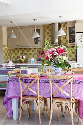 blumenstrauss auf tisch mit bunter tischdecke und alte holzst hle in moderner k che. Black Bedroom Furniture Sets. Home Design Ideas