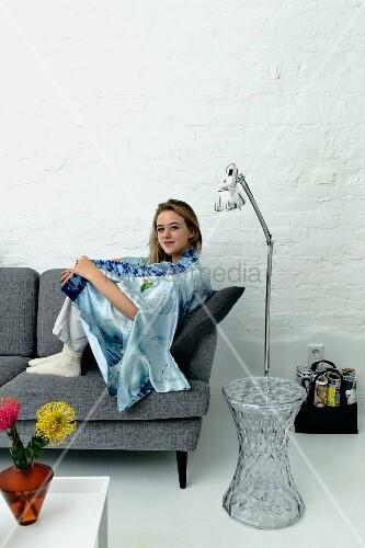 Junge Frau Auf Grauem Retro Sofa Transparenter Beistelltisch Und Edelstahl Stehleuchte Bild