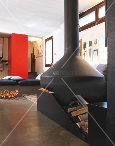 schwarzer kaminofen und holzlager in offenem wohnraum im. Black Bedroom Furniture Sets. Home Design Ideas