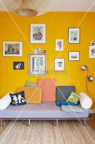 verschiedene polster auf schlichter tagesliege vor gelber wand mit bildersammlung bild kaufen. Black Bedroom Furniture Sets. Home Design Ideas