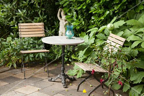 tisch und gartenst hle auf von gr npflanzen gesch tzter terrasse steinstatue im hintergrund. Black Bedroom Furniture Sets. Home Design Ideas