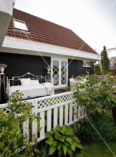 Blick von garten auf terrasse mit bett aus weissem metall - Holzwand garten ...