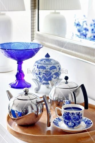 verchromte teekannen und blau weisses geschirr auf einem. Black Bedroom Furniture Sets. Home Design Ideas