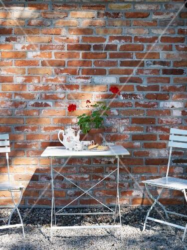 weisser gartentisch mit st hlen vor backsteinfassade bild kaufen living4media. Black Bedroom Furniture Sets. Home Design Ideas