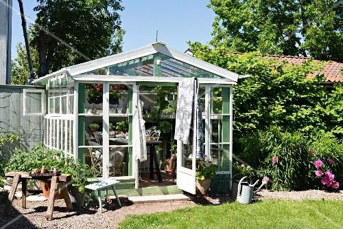 gew chshaus aus recyclingmaterial in sommerlichem garten bild kaufen living4media. Black Bedroom Furniture Sets. Home Design Ideas