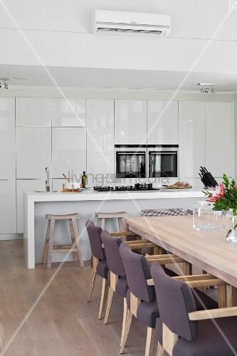 essplatz mit gepolsterten st hlen an holztisch im hintergrund offene k che minimalistische. Black Bedroom Furniture Sets. Home Design Ideas