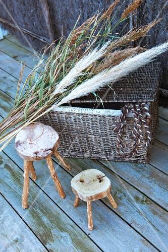 rustikale holzschemel neben rattankorb mit deckel und pampasgras auf holzdeck bild kaufen. Black Bedroom Furniture Sets. Home Design Ideas