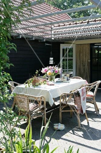 blumenstrauss auf tisch mit weisser tischdecke unter pergola einer sonnenbeschienenen terrasse. Black Bedroom Furniture Sets. Home Design Ideas