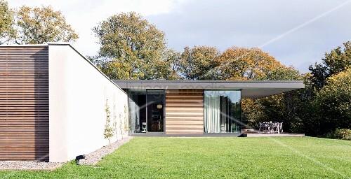 rasenfl che vor modernem wohnhaus mit holz glasfassade und auskragendem dach ber terrasse. Black Bedroom Furniture Sets. Home Design Ideas