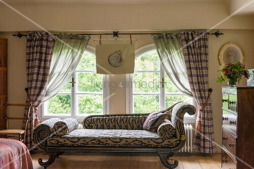 antike chaiselongue mit ikat muster vor rundbogenfenster. Black Bedroom Furniture Sets. Home Design Ideas
