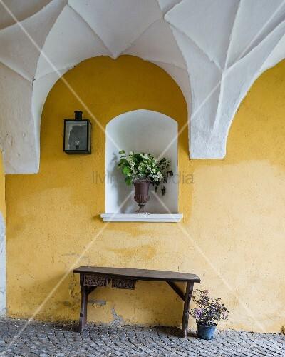 rustikale holzbank vor gelb gestrichener wand nische mit blumenstrauss im durchgang mit weisser. Black Bedroom Furniture Sets. Home Design Ideas