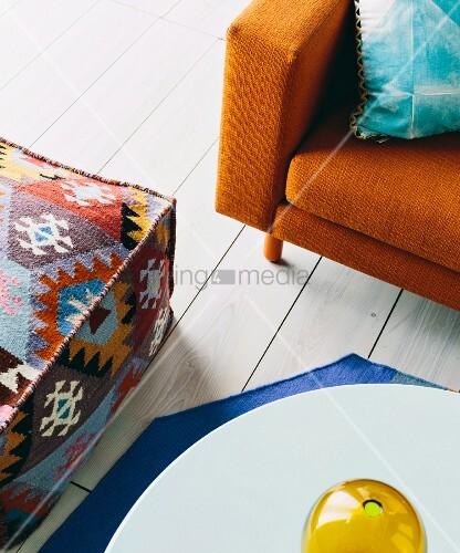oangefarbeners retrosofa ethno sitzpouf und couchtisch auf wei em dielenfu boden bild kaufen. Black Bedroom Furniture Sets. Home Design Ideas
