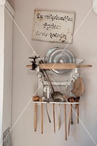 gestell mit vintage kuchenutensilien an pastellrosa