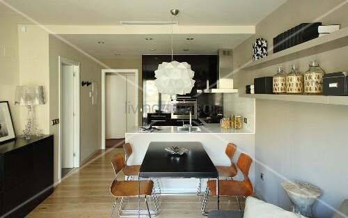 tisch mit schwarzer platte und holz schalenst hle vor theke in offener k che bild kaufen. Black Bedroom Furniture Sets. Home Design Ideas