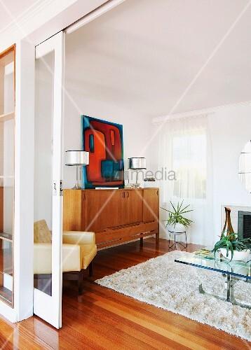 offene schiebet r mit blick ins wohnzimmer flokatiteppich auf holzboden seitlich sideboard aus. Black Bedroom Furniture Sets. Home Design Ideas