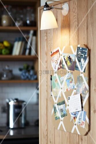 wandboard mit postkarten und fotos beleuchtet von einer lampe auf. Black Bedroom Furniture Sets. Home Design Ideas