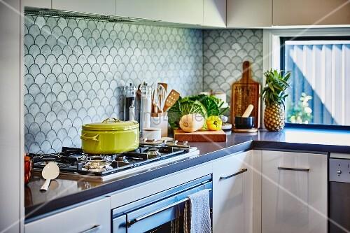 Weiße Küche mit KüchenzeileÜbereck, Gaskochfeld und Spritzschutz mit Fischschuppenmuster u2013 Bild