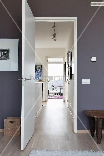 raum mit dunkelgrauen w nden und offener t r blick durch schmalen gang ins arbeitszimmer bild. Black Bedroom Furniture Sets. Home Design Ideas
