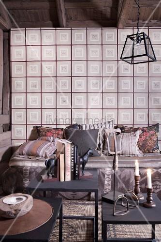 beistelltische aus metall mit kerzen und b chern gem tliche sitzbank mit kissen vor wand mit. Black Bedroom Furniture Sets. Home Design Ideas