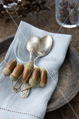 Leinenserviette mit Silberlöffel und mit Ring aus Eicheln