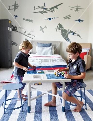 zwei kinder spielen im kinderzimmer am tisch auf blauwei gestreiftem teppich im hintergrund. Black Bedroom Furniture Sets. Home Design Ideas